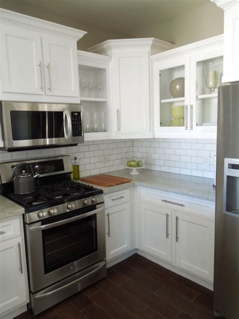 white kitchen cabinets with stainless appliances white cabinets staggered height cabinets glass front
