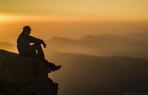 photo of a silhouette photo of sitting on edge of rock mountain
