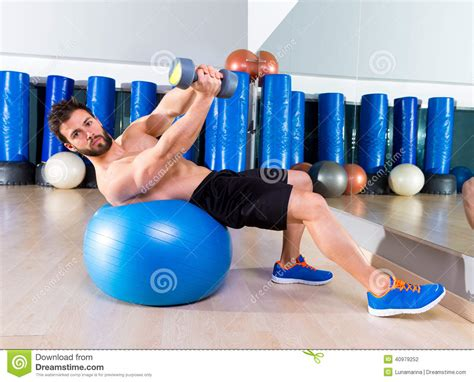 exercise ball bench press dumbbell bench press on fit ball man workout at gym stock