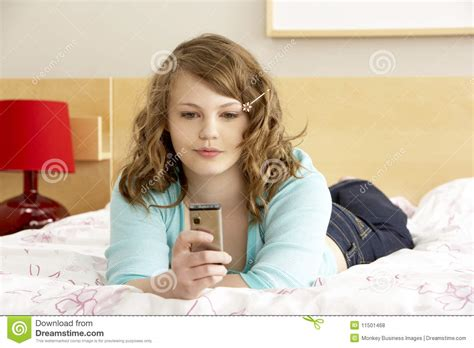 girl with mobile phone in bedroom stock photo image teenage girl in bedroom with mobile phone royalty free