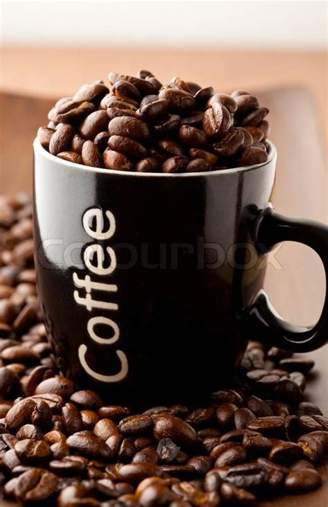 Tumbler Coffee Bean up of coffee beans and a coffee mug stock photo