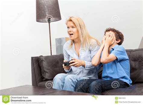 the last mama on the couch play mother and son playing a video game stock photography