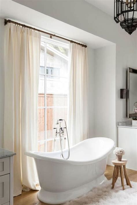 shower curtain in or out of tub silver bathtub in front of factory windows transitional