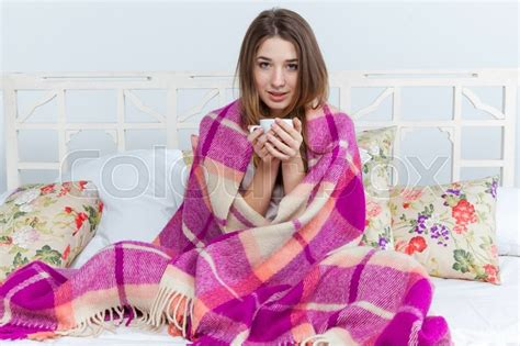 wolldecke sofa sick covered with blanket holding cup of tea sitting
