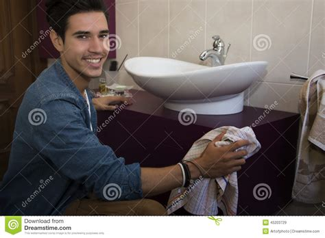 man cleaning bathroom cheerful young man cleaning the bathroom stock photo