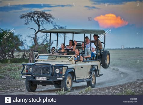 Safari Auto by 4x4 Safari Car With Tourists And Guide During Sunset In