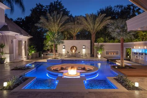 luxurious indoor and outdoor oasis pool house by icrave tropical pool with sunken fire pit seating area hgtv