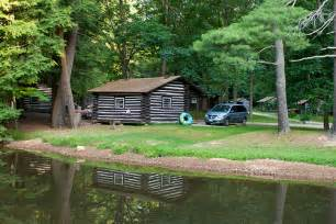 a log cabin is reflected in the fishing pond at cook