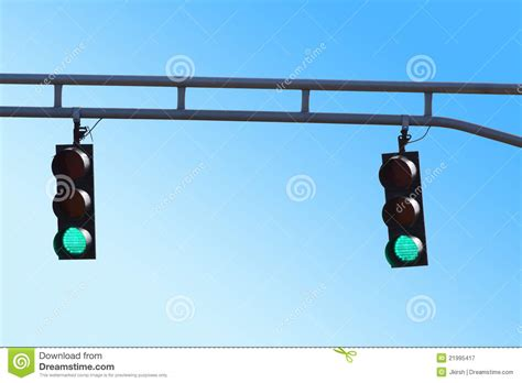green light driving two hanging traffic signals with green lights stock image