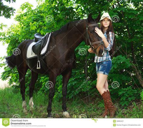 retrato exterior da vaqueira bonita com o cavalo no verde