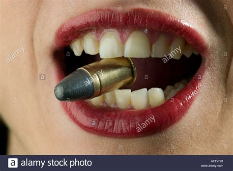 Biting The Bullet up of womans biting bullet held in teeth stock