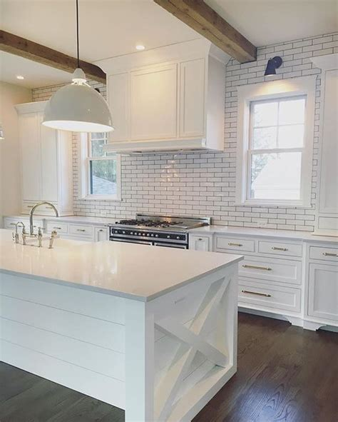 white symmetrical kitchen range with natural wooden kitchen with wood beams white cabinets subway tile and