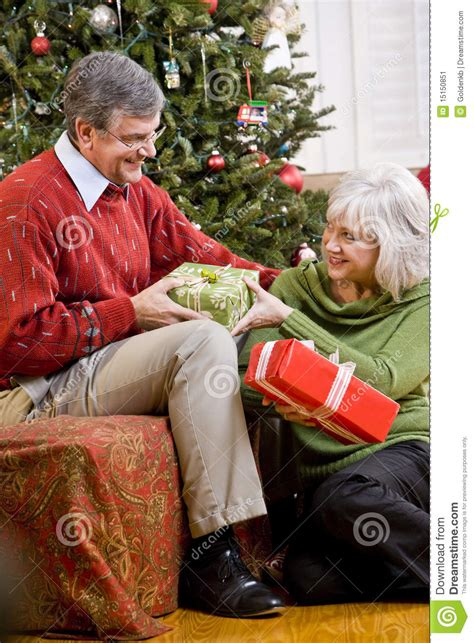 senior couple exchanging gifts by christmas tree stock