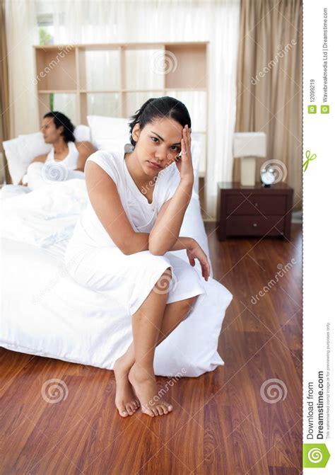 lovers in bed upset lovers sitting on the bed separately royalty free