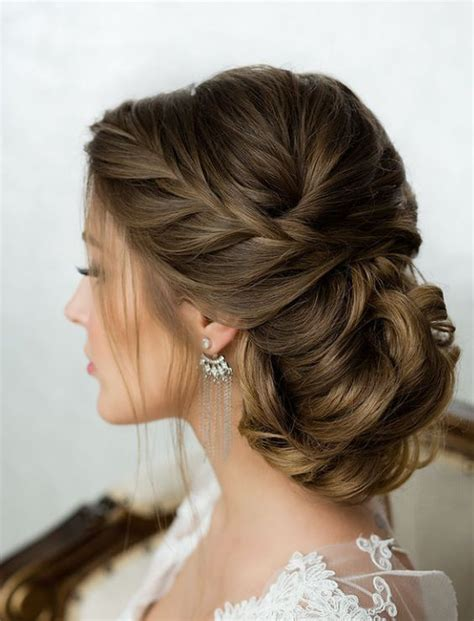 wedding hair bun on the side side braid low wavy bun wedding hairstyle updo