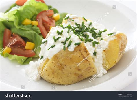 cottage cheese potatoes baked potato with cottage cheese chives and fresh salad on a white plate stock photo 111727034