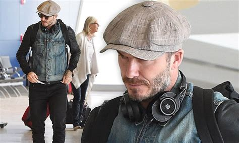 David Beckham arrives at JFK airport and cuts a rugged