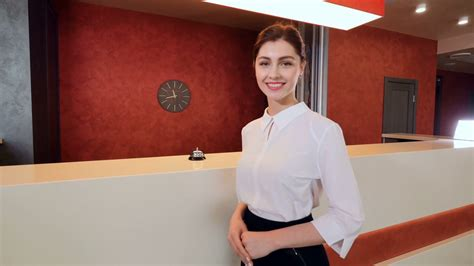 friendly smiling hotel receptionist greeting hotel guest