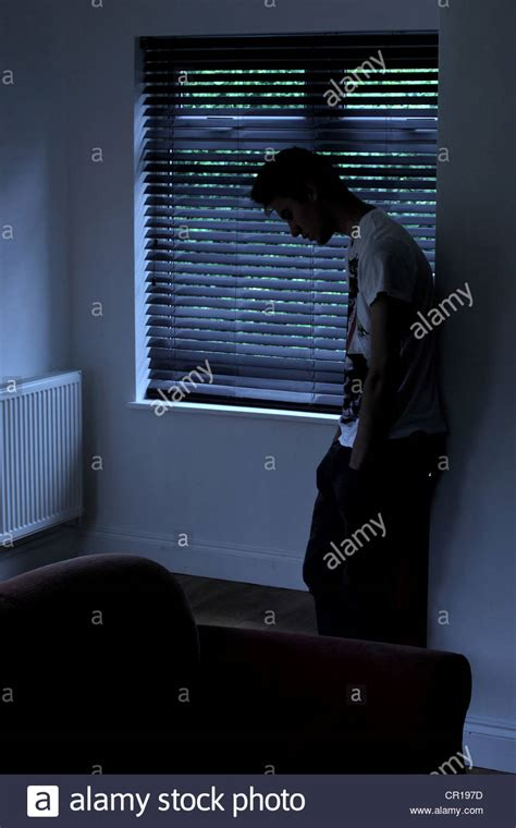 looking out from my lonely room sitting in a room looking out through a window blind stock photo royalty free