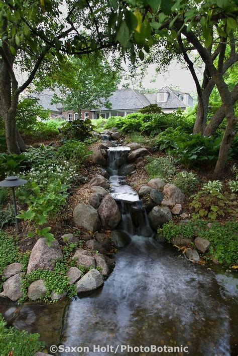 backyard waterfall and stream waterfall to pond with stream edged with stone through