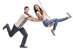 pushing a swing delighted young man swinging on a wooden swing stock photo