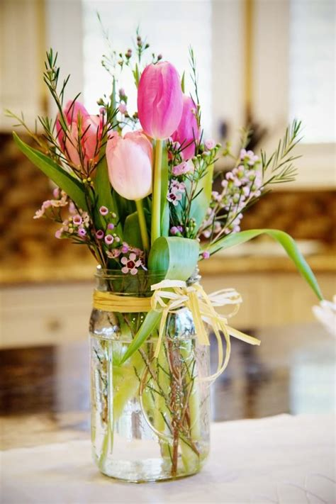 this centerpiece of tulips and wax flower is beautiful and bright the glass jar and raffia give