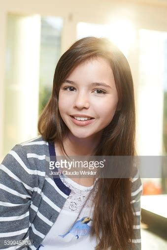 11 years old that has highlights at the bottom of their hair 11 years old girl at home back light smiling stock photo