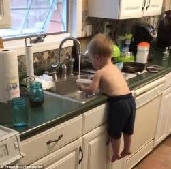 washing baby in kitchen sink toddler dangles sink and washes bowls on instagram daily mail