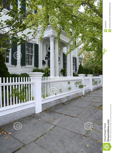 Cape Cod House Designs white picket fence by a typical federal style house stock