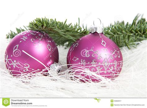 two pink christmas balls and pine tree over white