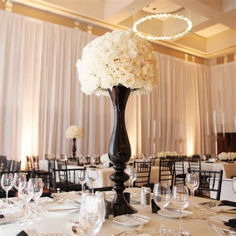 Black Vases For Wedding Centerpieces A Tall Black Vase With White Blooms Creates A Dramatic