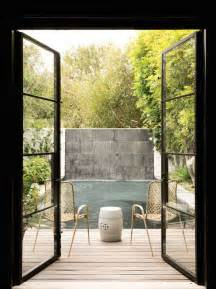 Steel french doors open onto the deck with woven chairs either side of