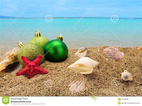 christmas balls and shells on sand with summer sea stock