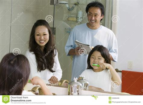 daughter in bathroom mirror reflection of family in bathroom getting ready for
