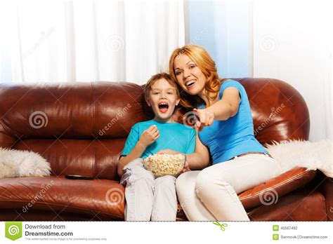 mom on sofa happy mother pointing at tv and son laughing stock photo