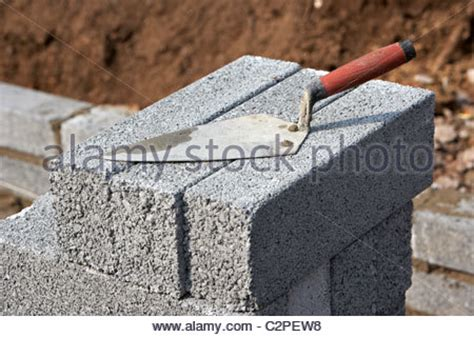 bricklayer with trowel building a wall with half cement