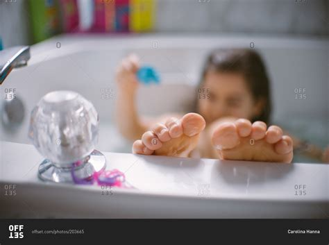 girls bathtub girl playing in the bathtub with feet on edge of tub stock