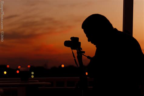 photo of a silhouette of photographer capturing the sunset