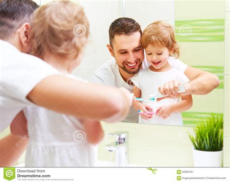 dad daughter in bathroom happy family father and child girl brushing her teeth in