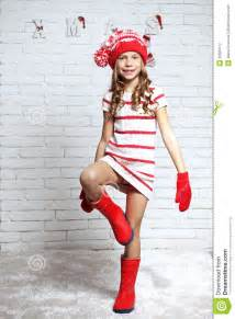 Little fashion girl in fashion christmas clothes posing over white
