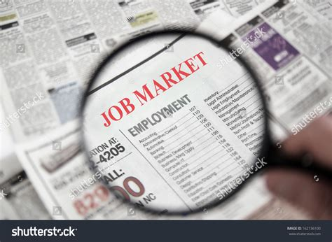 employment section of newspaper magnifying glass over newspaper classified section stock