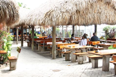 Tiki Huts Miami customers relax and enjoy their seafood while sitting the tiki huts that adorn the