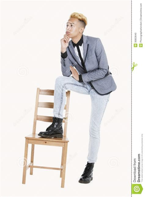 Thoughtful teenage boy standing with one leg on chair over gray background stock photo image