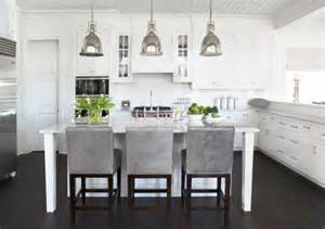 Pendant lights bring an antique touch to this modern white kitchen