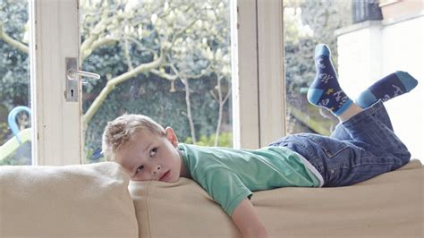 boy on couch staying home alone nspcc