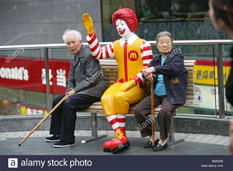 ronald mcdonald bench ronald mcdonald figure pensioners rest on a bench