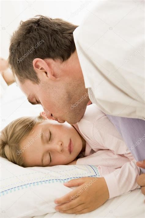 girls kissing in bed man waking young girl in bed with kiss stock photo
