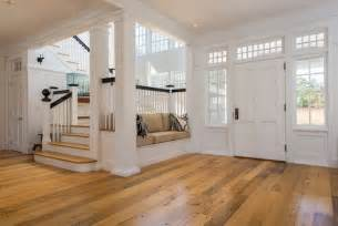 Simple yet elegant front entrance in white with wood flooring small