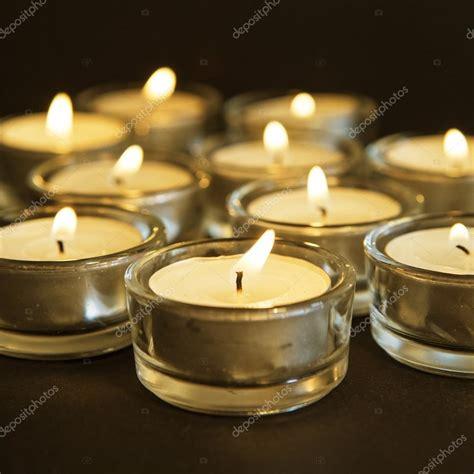 foto candele accese gruppo di candele accese su sfondo nero foto stock