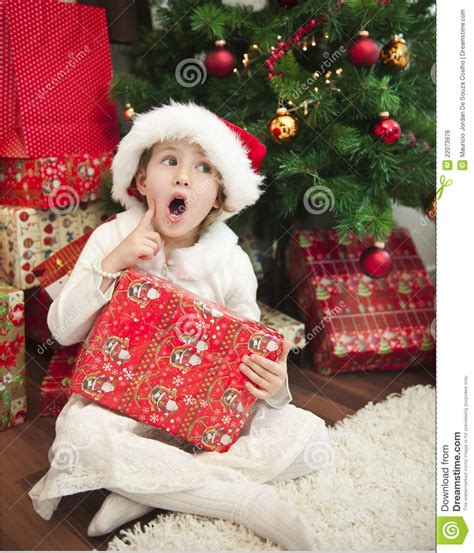 child with gift in front of christmas tree royalty free